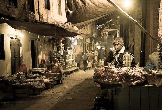 Flower vendor in narrow old city alley at night. Photo by Q.T. Luong.